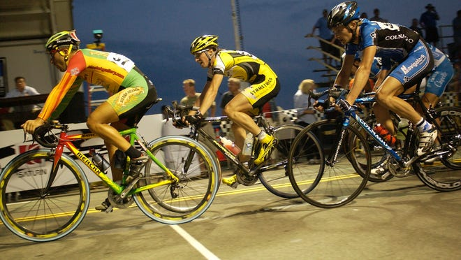 Cyclists race up Broad Street from Exchange Boulevard through the grandstand during the 2006 Saturn Rochester Twilight Criterium in downtown Rochester on June 24.