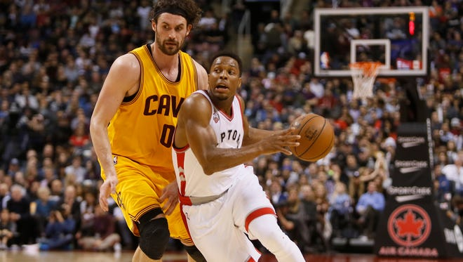Toronto Raptors guard Kyle Lowry (7) dribbles the ball past Cleveland Cavaliers forward Kevin Love (0) at the Air Canada Centre. The Raptors won 99-97.