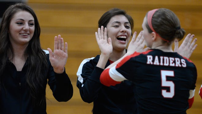 Cienna Doell (left) and Jaisah Lee, who both did not dress for the match, give high fives to Courtenay Parker (5) as the starting lineup is announced before facing Notre Dame.