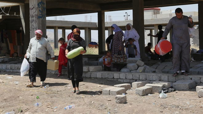 Displaced Iraqis from the Yazidi community settle under a building in central Dahuk, 260 miles northwest of Baghdad, on Aug. 14.