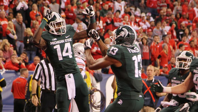 Michigan State wide receiver Tony Lippett (14) celebrates with teammate Bennie Fowler (13) after scoring a touchdown against Ohio State during the first half of the Big Ten Championship on Saturday at Lucas Oil Stadium.