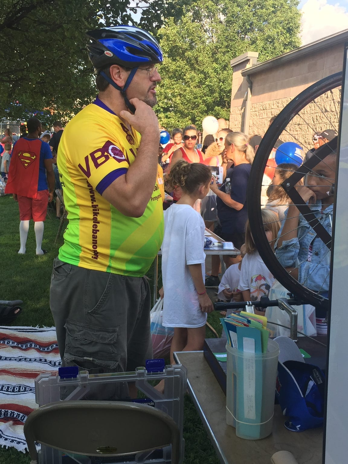 Dean Auchenbach, vice president of the Lebanon Valley Bicycle Coalition, demonstrates how to put on a helmet Aug. 1 during National Night Out on Guilford Street in Lebanon.