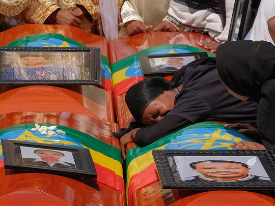 A woman lies on the coffin of her loved one during a memorial service for the passengers and crew who perished in the Ethiopian Airlines crash. All 157 passengers and crew were killed after the Boeing 737 MAX 8 plane came down six minutes after taking off from Bole Airport.