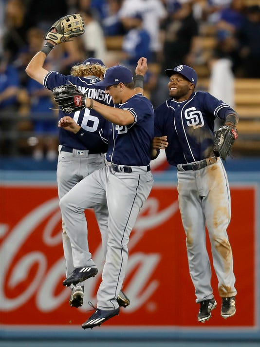 San Diego Padres left fielder Travis Jankowski, left, right fielder Hunter Renfroe, center, and center fielder Manuel Margot celebrate the Padres' 4-0 win in a baseball game against the Los Angeles Dodgers, Tuesday, April 4, 2017, in Los Angeles. (AP Photo/Ryan Kang)