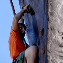 One scout plots out his next move near the top of one of the climbing walls in the middle of The Hub, Tuesday, August 4, 2015, at the 100th National Order of the Arrow Conference on the campus of Michigan State University.