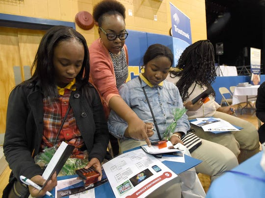 Canton English 1 teacher Anita Nelson, back, helps, from left, Quinyatta Bailey, 15, Daria Bradfield, 15, and Aryanna Bouldin, 14, with their checkbooks during the Reality Fair for 208 ninth graders in the Canton High School gym.