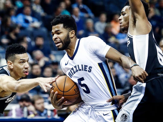 Memphis Grizzlies guard Andrew Harrison (middle) drives the lane against San Antonio Spurs defenders Danny Green (left) and Dejounte Murray (right) during first quarter action at the FedExForum in Memphis, Tenn., Wednesday, January 24, 2018.