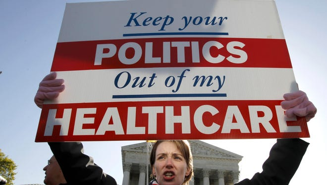 FILE - In this March 27, 2012 file photo, Amy Brighton from Medina, Ohio, who opposes health care reform, holds a sign in front of the Supreme Court in Washington during a rally as the court continues arguments on the health care law signed by President Barack Obama. Most Americans want the Supreme Court to side with the government when it decides whether the feds can continue subsidizing insurance premiums in all 50 states under President Barack Obama's health care law, according to polls in recent months. (AP Photo/Charles Dharapak, File)