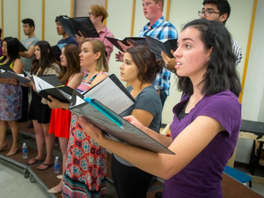 "NMSU Music Education major Mikayla Twitchell, right, and other singers from NMSU's University Singers rehearse Stephen Paulus'  ""The Old Church""  while John Flanery conducts."
