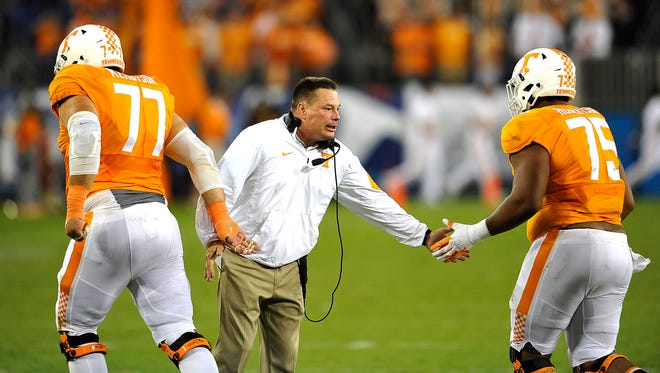 Coach Butch Jones greets Tennessee offensive linemen Kyler Kerbyson (77) and Jashon Robertson (75) during the Bowling Green game at Nissan Stadium on Sept. 5.