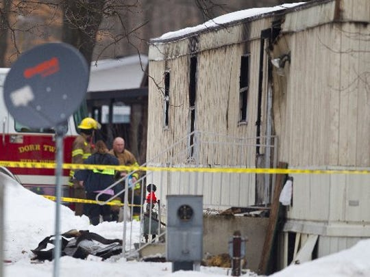 Emergency personnel investigate the scene of a fatal fire in Dorr Township, Mich., on March 10, 2015.