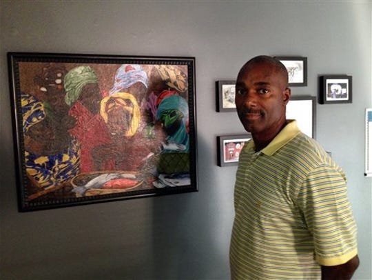 Ndume Olatushani stands with one of his paintings,