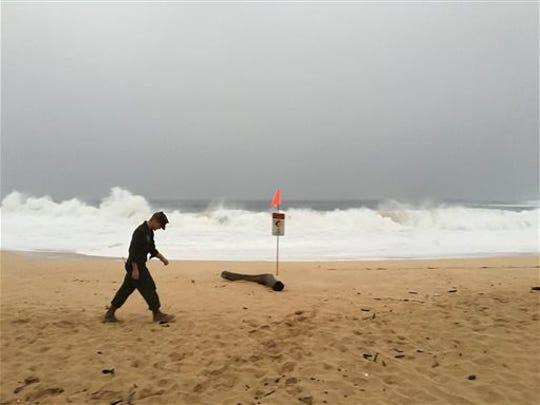 A U.S. Marine walks on the beach at Waimea Bay near Haleiwa, Hawaii, where two military helicopters crashed into the ocean about 2 miles offshore, Friday, Jan. 15, 2016. The helicopters carrying 12 crew members collided off the Hawaiian island of Oahu during a nighttime training mission, and rescuers are searching a debris field in choppy waters Friday, military officials said.