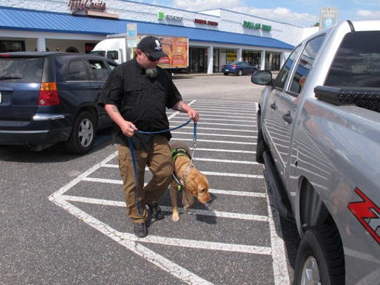 Army veteran Joe Aguirre and his service dog, Munger, walk back to their truck after lunch in Fayetteville, N.C.