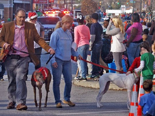 Children pet a greyhound that was in the 2015 Anderson Christmas Parade as part of Greyhound Crossroads entry.