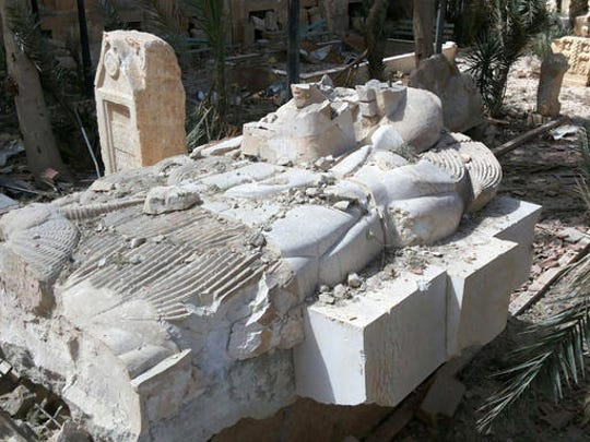 FILE - This file photo released March 27, 2016, by the Syrian official news agency SANA, shows a destroyed statue outside the damaged Palmyra Museum, in Palmyra city, central Syria. Palmyra, the archaeological gem that Islamic State fighters retook Sunday, Dec. 11, 2016, from Syrian troops, is a desert oasis surrounded by palm trees, and a UNESCO world heritage site, that boasts 2,000-year-old towering Roman-era colonnades and priceless artifacts. It is also a strategic crossroads linking the Syrian capital, Damascus, with the country's east and neighboring Iraq.