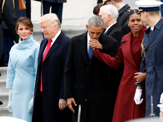 First lady Melania Trump stands with President Donald Trump as former President Barack Obama kisses the hand of his wife Michelle Obama, during a departure ceremony on the East Front of the U.S. Capitol, Friday, Jan. 20, 2017 in Washington.