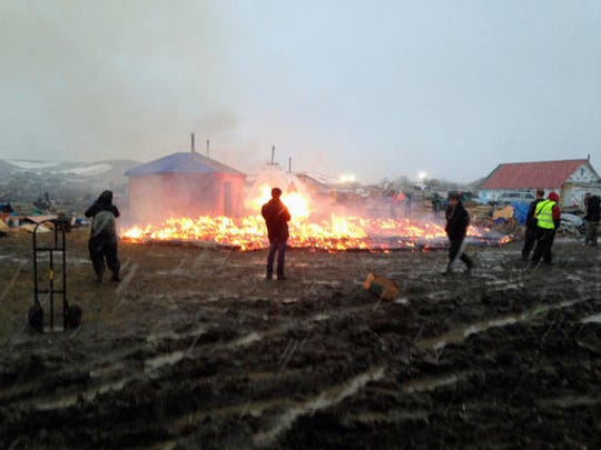 Dakota Access pipeline opponents burn structures in their main protest camp in southern North Dakota near Cannon Ball, N.D., on Wednesday, Feb. 22, 2017, as authorities prepare to shut down the camp in advance of spring flooding season.