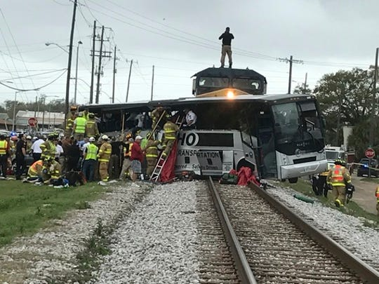 Biloxi firefighters assist injured passengers after their charter bus collided with a train in Biloxi, Miss., Tuesday, March 7, 2017.  Biloxi city spokesman Vincent Creel says emergency responders were still removing injured people from the bus more than 30 minutes after the crash.