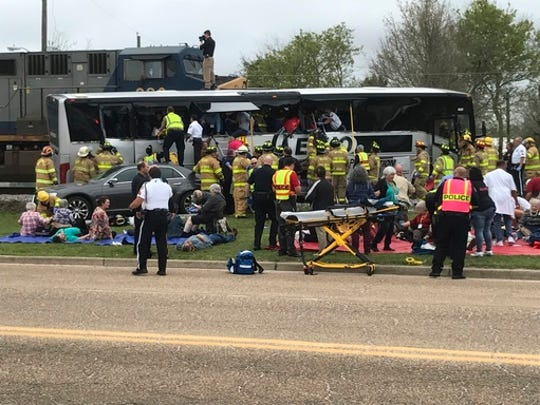 Emergency personnel assist injured passengers after their charter bus collided with a train in Biloxi, Miss., Tuesday, March 7, 2017.  Biloxi city spokesman Vincent Creel says emergency responders were still removing injured people from the bus more than 30 minutes after the crash