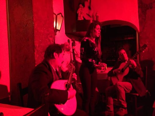 This Jan. 21, 2017 photo shows singer Cuca Roseta, (standing), bathed in red light during a fado performance at Clube de Fado in Lisbon, accompanied on the left by Mario Pacheco on the 12-string Portuguese guitar and another musician on the right playing a conventional guitar. Lisbon is home to numerous clubs where fado, a soulful, melancholy genre of Portuguese folk music, is performed nightly.