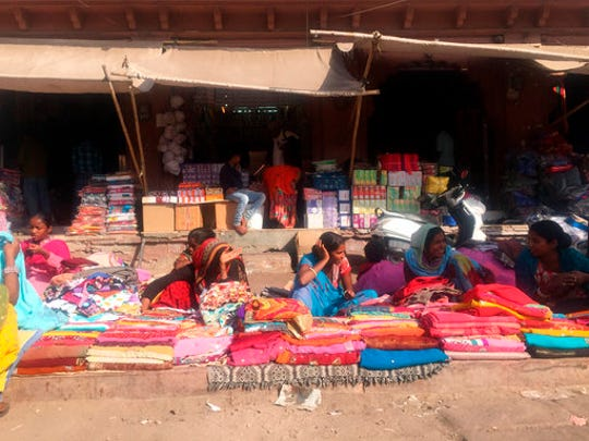 In this 2017 photo women sell brightly colored textiles