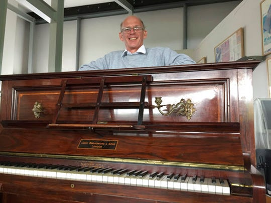 """Piano tuner Martin Backhouse with the piano where he found a stash of gold, smiles in Ludlow Museum in Ludlow, England Thursday April 20, 2017,  As a mystery surrounds the identity of the rightful heirs to a treasure trove of gold coins . British officials say they have been unable to trace the rightful heirs to a trove of gold coins  worth a """"life-changing"""" amount of money. The school that owns the piano and the tuner who found the gold are now in line for a windfall after a coroner investigating the find declared it treasure."""