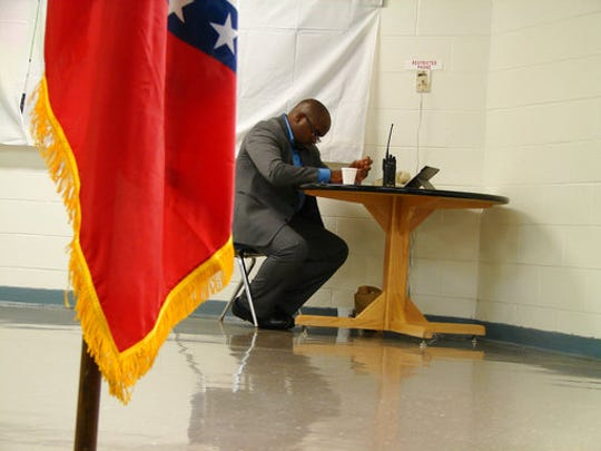 Solomon Graves, a spokesman for the Arkansas Department of Correction, waits at a desk behind an Arkansas flag for a telephone call with news from the death chamber at the Cummins Unit prison on Thursday, April 20, 2017. The U.S. Supreme Court rejected stay requests from Ledell Lee, allowing his execution to proceed at the prison near Varner, Ark.