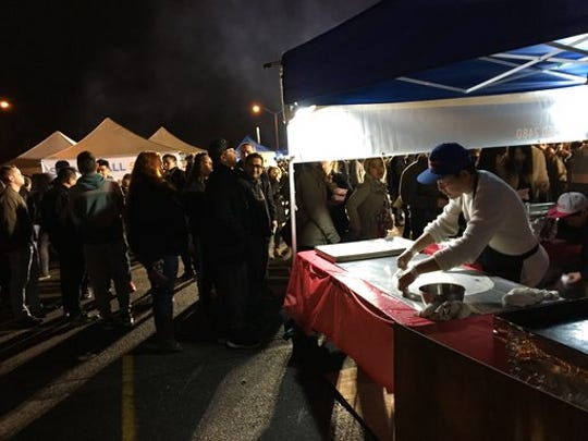 This April 22, 2017 photo shows a man preparing a large crepe used in a Burmese dish sold at the Queens Night Market in New York City's Corona, Queens, neighborhood. The market showcases about 50 food vendors, many of them immigrants selling examples of cuisine from their home countries, and is modeled on traditional night markets found in Asia. Similar night markets are popping up in other cities around the U.S.