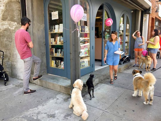 This April 29, 2017 photo shows people (and dogs) outside the new Books Are Magic bookstore in Brooklyn, New York, on the day it opened. The store is owned by novelist Emma Straub and her husband, who decided to open the store after another beloved neighborhood bookstore closed. Straub is one of a number of authors who own bookstores around the country, including Ann Patchett and Jeff Kinney.