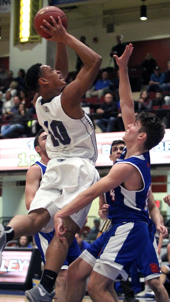 Putnam Valley's Darnell Shillingford drives on Blind Brook's Alex Feuerstein during their Class B semifinal at the Westchester County Center Feb. 26, 2018.