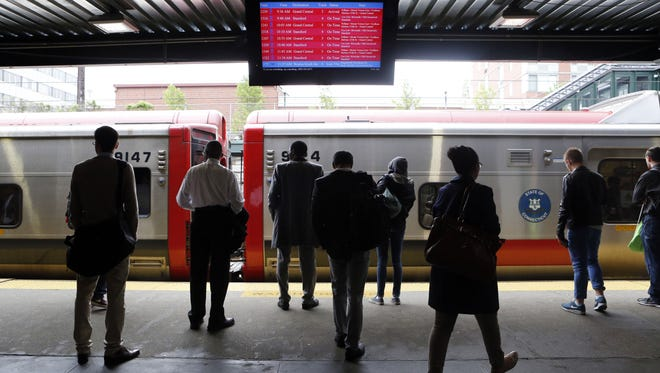 Commuters approach a Metro-North New Haven Line train May 16, 2014, at the New Rochelle station.