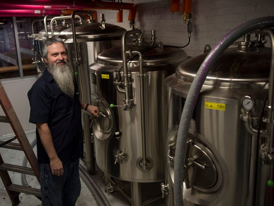 Owner John Mills II poses for a portrait near his brew