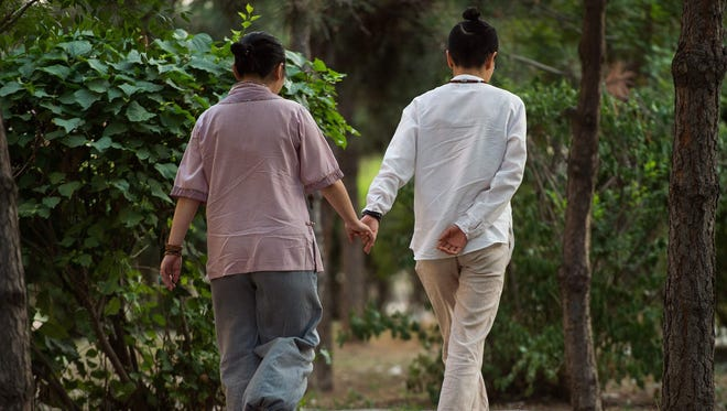 In this picture taken on July 3, 2017 Xiaoxiong (R) and Xiaojing (L) walk in a park in Sheynyang. When Xiaoxiong and her lesbian lover wanted to hide their relationship from their parents, they decided to find men willing to marry them. They had a specific type in mind: Gay. Homosexuality was classified as a mental illness in China until 2001 and a crime until 1997, and authorities have arrested gay rights activists.  / AFP PHOTO / NICOLAS ASFOURI / TO GO WITH: China-gay-marriage, FEATURE by Joanna CHIUNICOLAS ASFOURI/AFP/Getty Images ORIG FILE ID: AFP_U914O