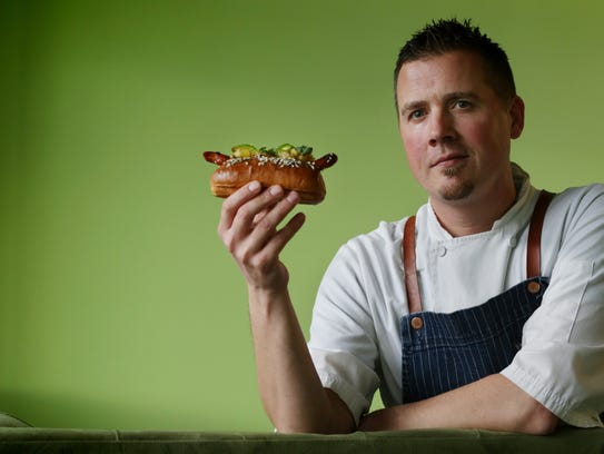Doug Hewitt of Chartreuse with his hot dog that will be sold at Chartreuse during Hot Dogs for Dogs.