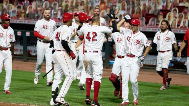 Cincinnati Reds right fielder Nick Castellanos, center, celebrates with teammates after scoring the game-ending run on a wild pitch from Chicago Cubs relief pitcher Craig Kimbrel in the seventh inning of the second game of a doubleheader at Great American Ball Park in Cincinnati on Saturday night, Aug. 29, 2020.