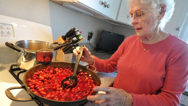 Lois Murphy, 89, stirs the beach plums in her Houghs Neck kitchen.