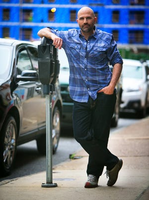Charles Ebbie Alfree III wears a purple plaid, button-down, rolled-up sleeves shirt by INC International Concepts; dark blue straight jeans by Levi's; funky grey shoes by KEEN.