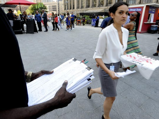 A petitioner, left, asks voters to sign petitions during lunch at Campus Martius Park in Detroit in 2017.