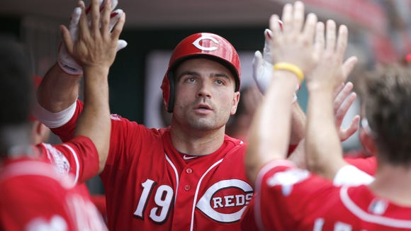 Cincinnati Reds first baseman Joey Votto (19) is congratulated in the dugout after hitting a two-run home run in the third inning during the Major League Baseball game between the Cincinnati Reds and the Washington Nationals Saturday.