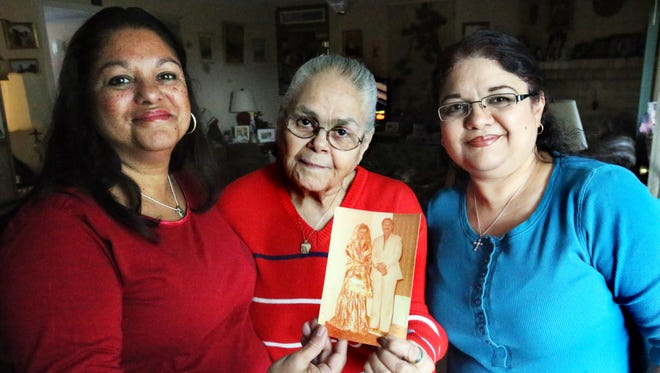 Elizabeth Derrick, center, and daughters Debbie Boroff, left, and Margaret Mullis, right, show a faded wedding photograph of third daughter Samar Saqib Butt, whom they will reunite with in Pakistan.