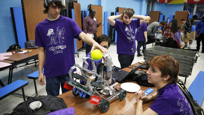 Christian Ackman, left, and Brittany Roberts of team OctoπRates, test their SAIL High School robot before competing in the R³ robotics competition.