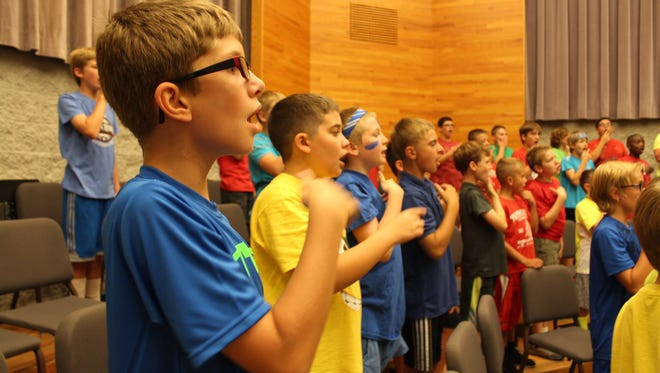 James Anderson of St. Stephen and his peers from The St. John's Boys' Choir participating in vocal exercises.
