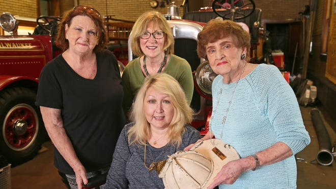 At the Milwaukee Fire Historical Society museum, James McCarthy's family holds his helmet, bent when the ceiling caved in during a fire at the Cathedral of St. John the Evangelist in 1935. Seated is Maureen Fitzgerald-Ivans of Elm Grove and behind her (from left) are Susie Fitzgerald of Greenfield, Colleen Fitzgerald of Glendale and Marie Fitzgerald of Elm Grove, the women's mother and the daughter of James McCarthy.