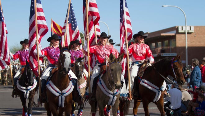 The Bridwell Girls hold the flags as the parade's Honor Guard during the 62nd Parada Del Sol Parade from 2015 in Old Town Scottsdale.