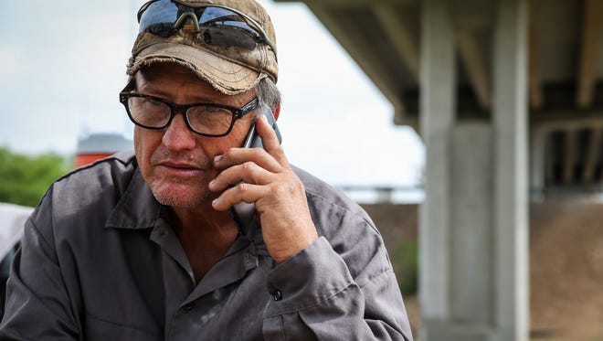 Mike Brannon talks to a potential employer outside of his tent under the Houston Harte Expressway in San Angelo last month.
