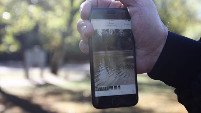Bill Wade holds a phone with a picture of how high the water was Monday at the Pickens County campground where he, and 16 others, were evacuated on small rafts.