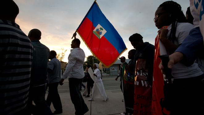 Haitian-Americans carry Haitian flags and signs as they march to commemorate the eighth anniversary of the Haitian earthquake, Friday, Jan. 12, 2018, in Miami.