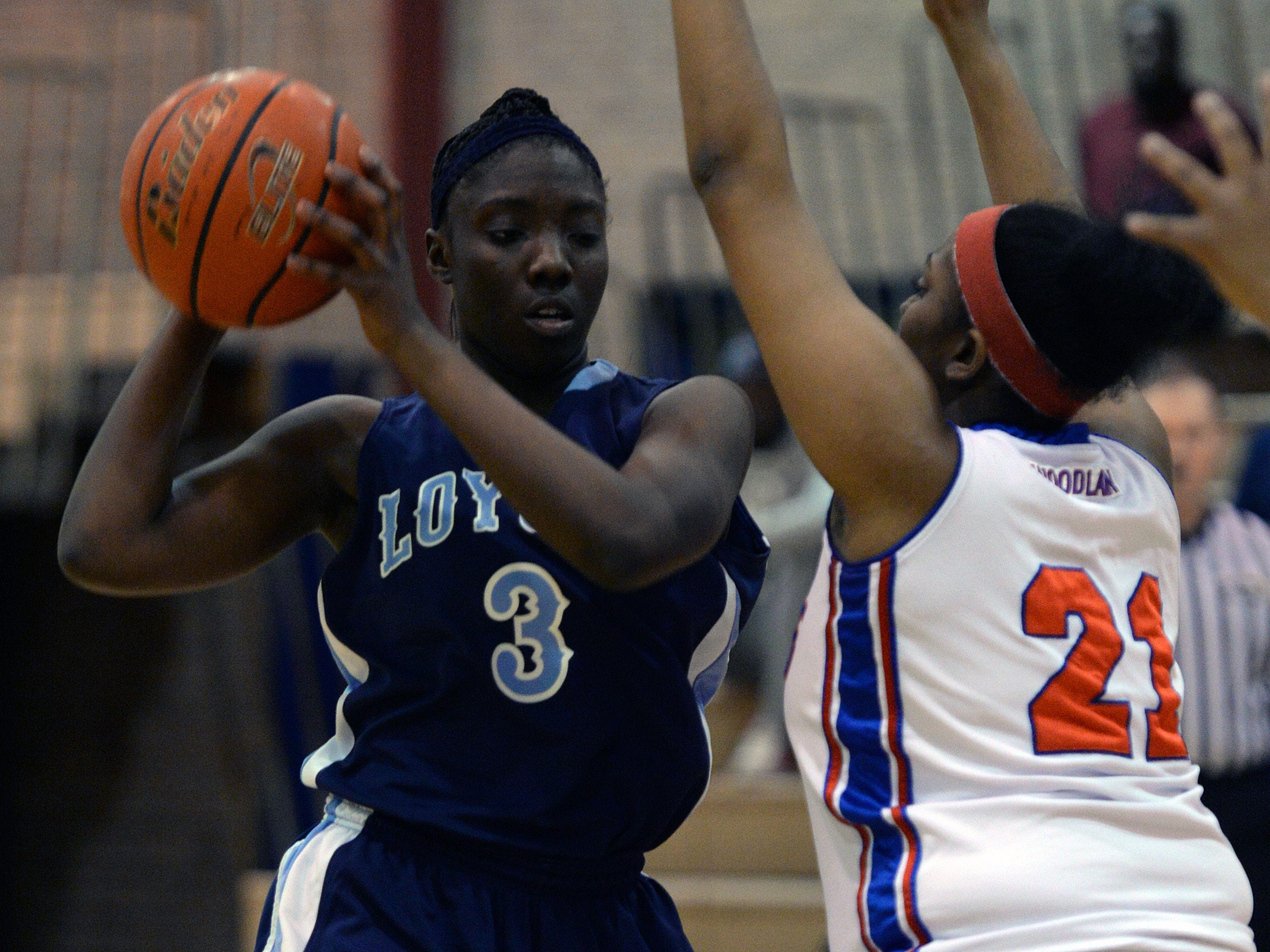 Loyola's Amber Smith sets up against Woodlawn's L. Whitaker.