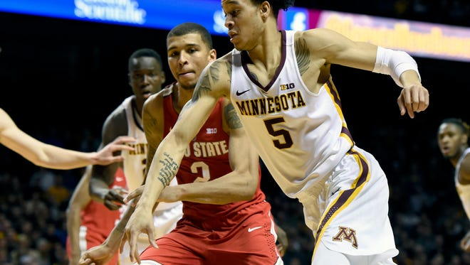 Minnesota guard Amir Coffey (5) drives against Ohio State forward Marc Loving (2) during the second half of an NCAA college basketball game Sunday, Jan. 8, 2017, in Minneapolis. Minnesota won 78-68. (AP Photo/Hannah Foslien)